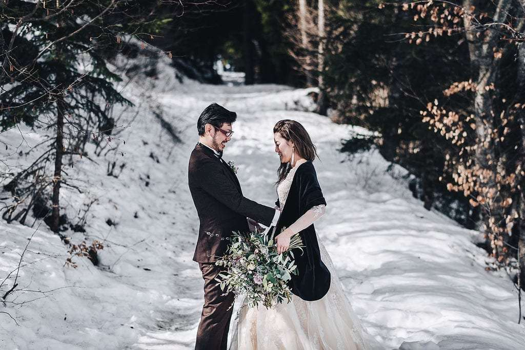 A Japanese newlywed couple looking to each other in a snowy forest on south tyrol