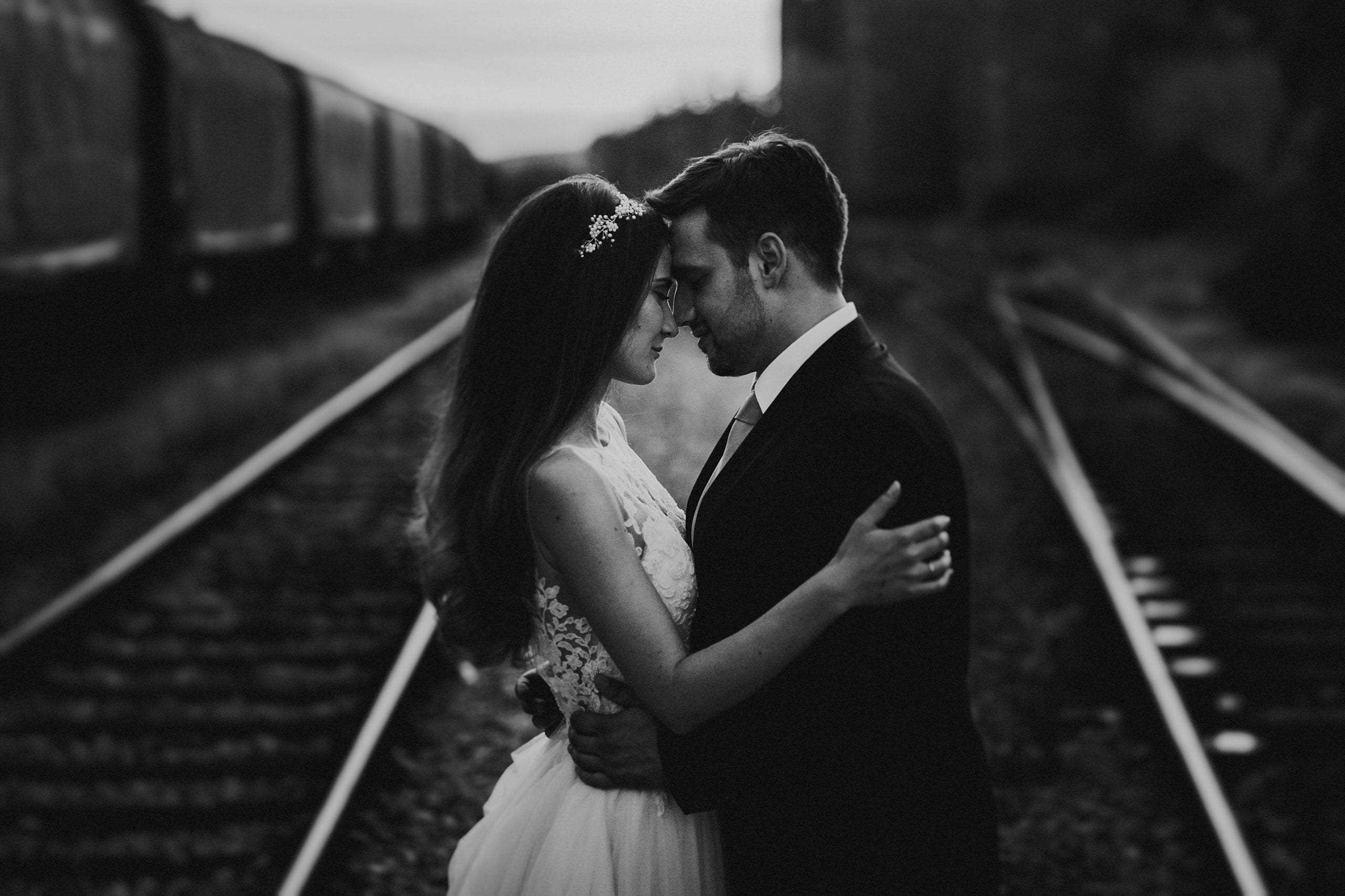A couple standing on train tracks during an Elopement in Italy.