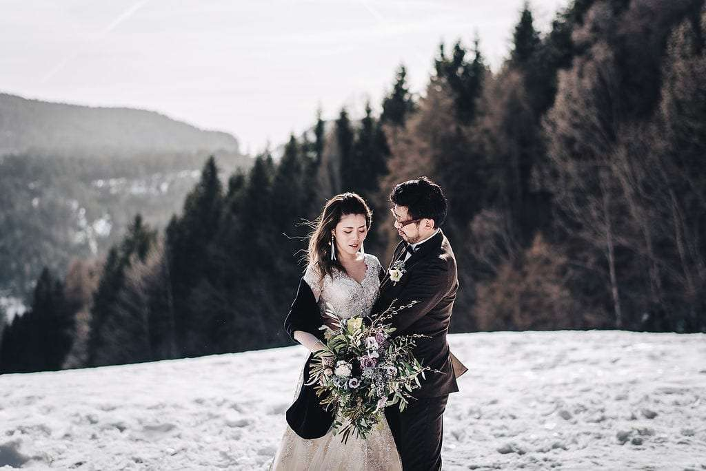 Newlywed couple hugging in South Tyrol over the snow