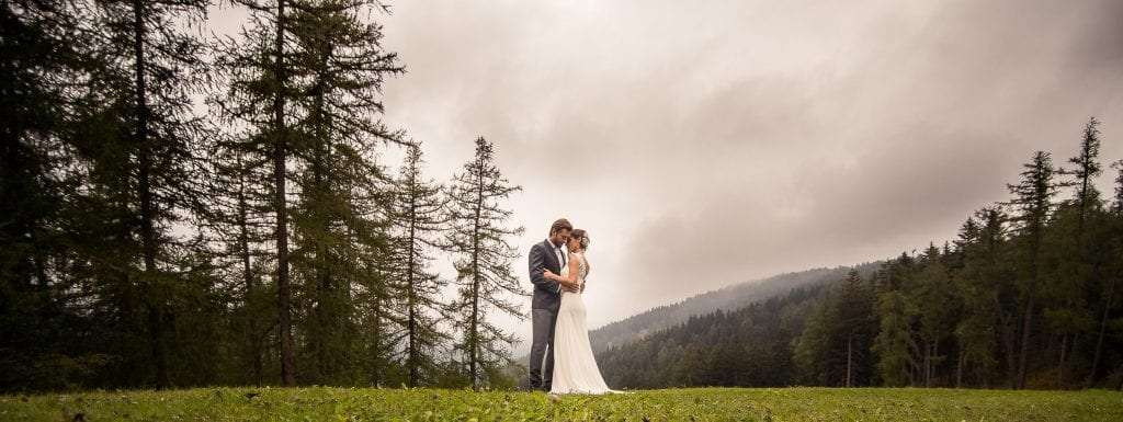 newlywed couple hugging each other in front of the mountains