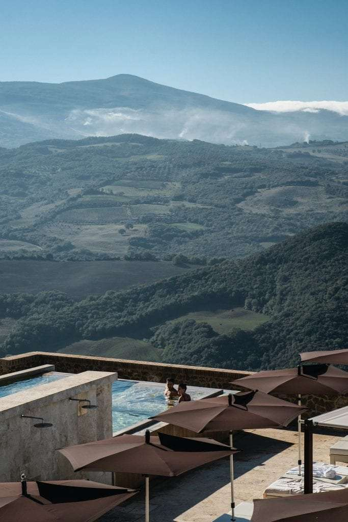 A couple inside a swimming pool in a tuscan villa.