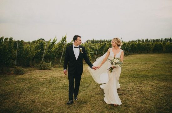 A couple holding hands inside a vineyard in Tuscany.