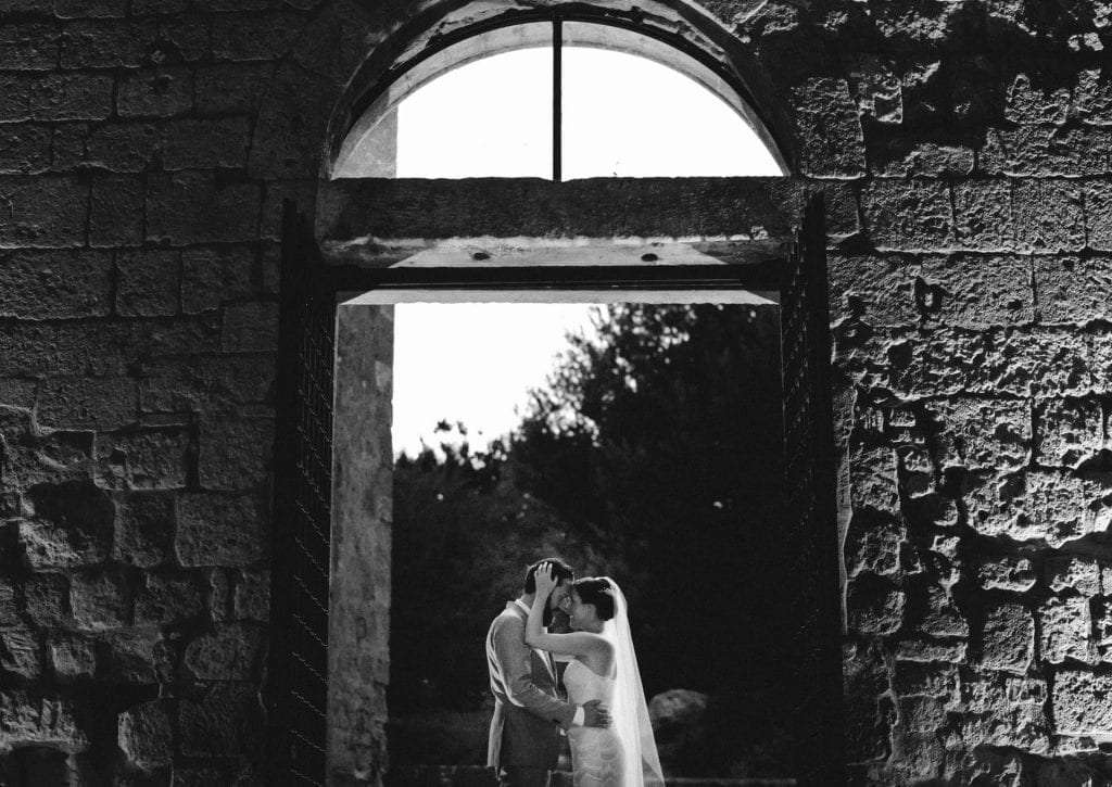 A newlywed couple hugging each other in an old Abbey in Italy.