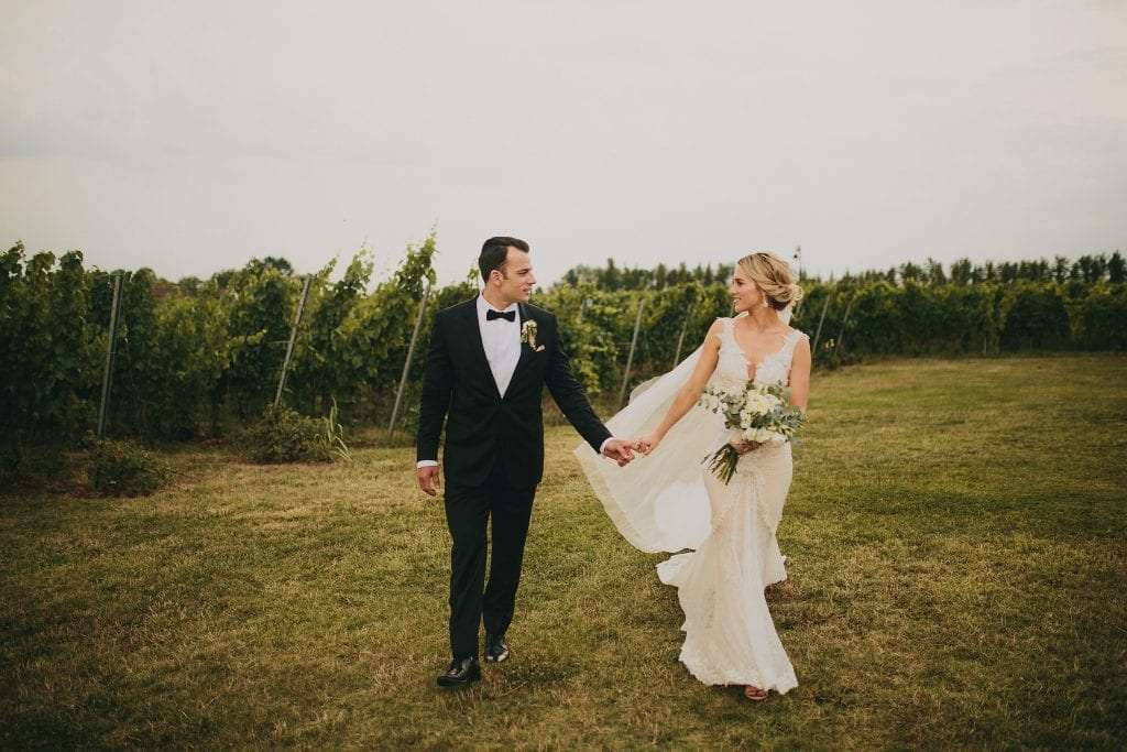 a couple walks next to a vineyard in Italy
