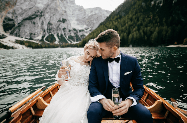A newlywed couple on a boat on the Lake Braies on Dolomites.